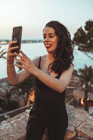 Beautiful girl taking a selfie near the beach with the warm light of the sunset evening Reklamní fotografie
