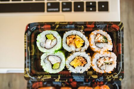 Several tasty sushi rolls and laptop at wooden table
