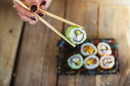 Unrecognized woman and tasty sushi rolls at wooden table, space for text. Food delivery