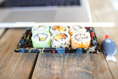 Top View of Vintage handmade Wood Table with Asian Sushi and laptop Reklamní fotografie - 127261272