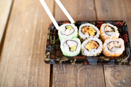 Tasty sushi rolls at wooden table, space for text. Food delivery