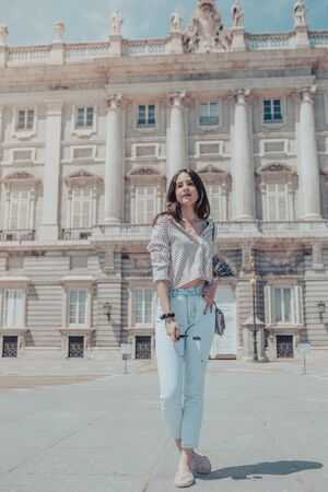 Beautiful young tourist woman posing near Royal Palace of Madrid, Spain