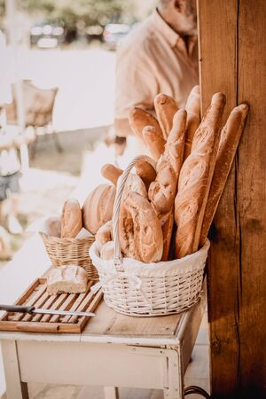 Variety of fresh homemade grain bread in a wicker basket, cutting board and knife on the outside