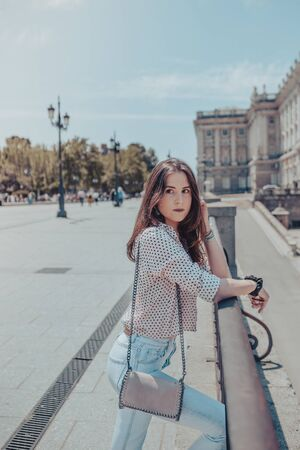 Beautiful young woman with a purse resting on a railing near Royal Palace of Madrid, Spain Reklamní fotografie