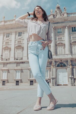 Beautiful tourist woman posing and sticking out tongue near Royal Palace of Madrid, Spain