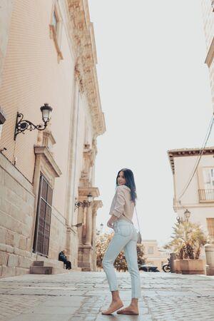 Full length back rear of young woman. Girl posing on the street. Reklamní fotografie - 127261283
