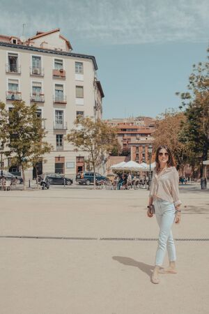 Full body portrait of beautiful young tourist woman visiting the city of Madrid, Spain. Model posing in the street.