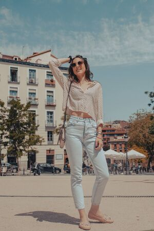 Portrait of beautiful young tourist woman visiting the city of Madrid, Spain. Model with sunglasses smiling and stroking her hair. Girl posing on the street.