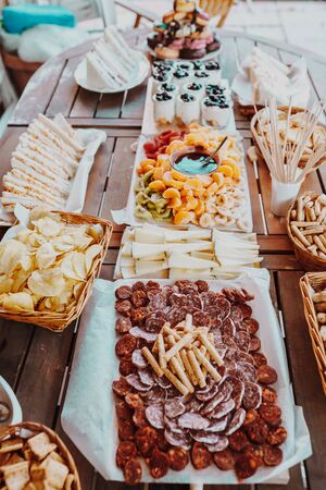 Typical spanish tapas concept. Concept include variety slices serrano ham, chorizo, salami, cheese, chips, bread, sandwiches, donuts, yogurt, fruits foundie tangerine, banana, kiwi, blueberries, strawberries on a wooden table.