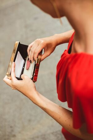 Unrecognizable woman with red dress looking the smartphone in her golden purse