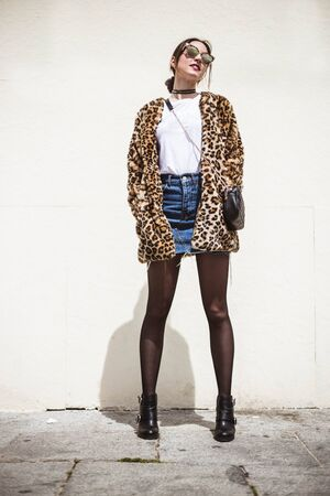 Outdoor full body fashion portrait of elegant woman wearing trendy animal, leopard print faux fur coat, denim skirt, stylish sunglasses posing on white background. Copy, empty space for text