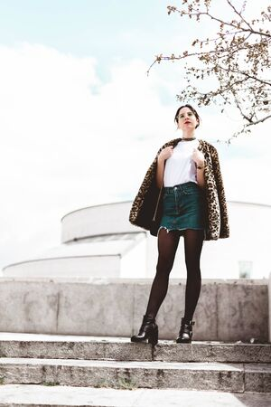 Stylish portrait of young woman smiling and wearing trendy animal, leopard print faux fur coat, fashion sunglasses, posing in european street city