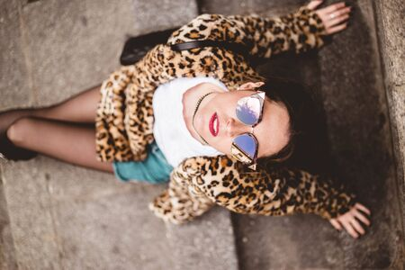 Top view of fashion portrait of young beautiful confident woman sitting and wearing trendy animal, leopard print faux fur coat, stylish sunglasses, looking at the sky, posing in street of city Imagens