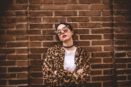 Stylish portrait of young serious model with crossed arms wearing trendy leopartd print faux fur coat, fashion sunglasses, posing on red brick wall texture grunge background Imagens