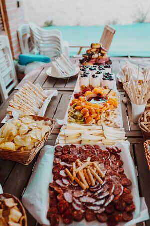 Typical spanish tapas concept. Concept include variety slices chorizo, salami, cheese, chips, bread, sandwiches, donuts, yogurt, fruits chocolate fondue tangerine, banana, kiwi, blueberries, strawberries on a wooden table.