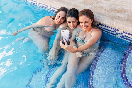 Portrait of beautiful young girlfriends sitting by the pool taking a selfie photo with mobile phone. Outdoor shot. Friendship concept