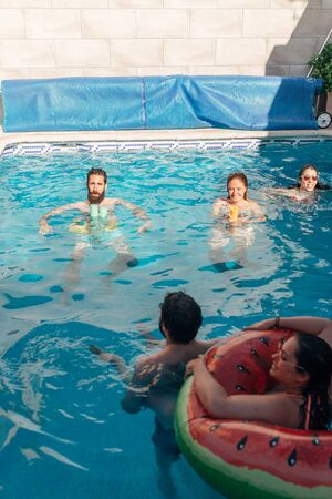 group of friends playing inside the pool enjoying the summer. Concept of friendship. Fun moments
