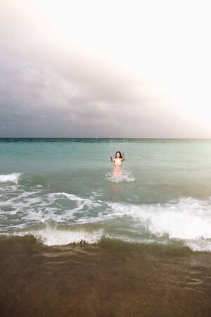 Girl with in pink bikini playing in blue clear water beach in a cloudy. Travel concept. day