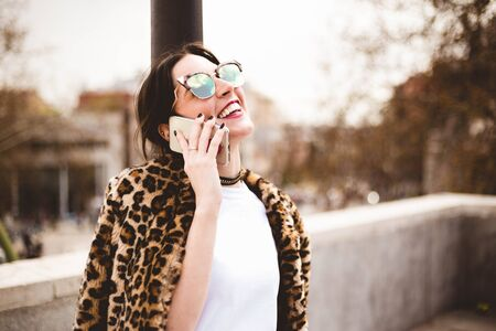 Cheerful woman talking on the phone wearing a wearing trendy animal, leopard print faux fur coat, stylish sunglasses, looking at the sky in street of European city. Copy space for text Imagens