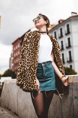 Stylish portrait of young model looking aside smiling and wearing trendy animal, leopard print faux fur coat, fashion sunglasses, posing in Madrid city