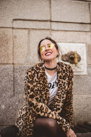 Lovely laughing brunette woman posing outdoor on old stone fountain background. Wearing stylish yellow glasses, trendy leopard print faux fur coat. Imagens