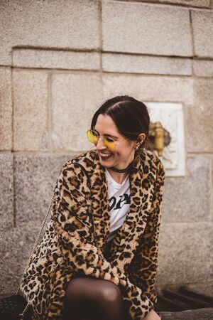 Lovely young laughing brunette woman posing outdoor on old stone fountain background. Wearing stylish yellow glasses, trendy leopard print faux fur coat.