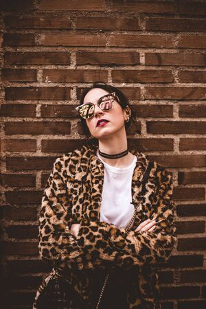 Stylish portrait of young serious woman with crossed arms wearing trendy leopartd print faux fur coat, fashion sunglasses, posing on red brick wall texture grunge background Imagens