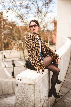 Fashion portrait of young beautiful serious woman sitting and wearing trendy animal, leopard print faux fur coat, stylish sunglasses, looking aside, posing in street of city Imagens
