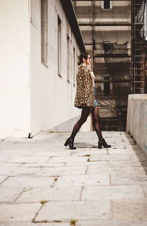 Outdoor full body fashion portrait of elegant model wearing trendy animal, leopard print faux fur coat, denim skirt, stylish sunglasses walking in the street