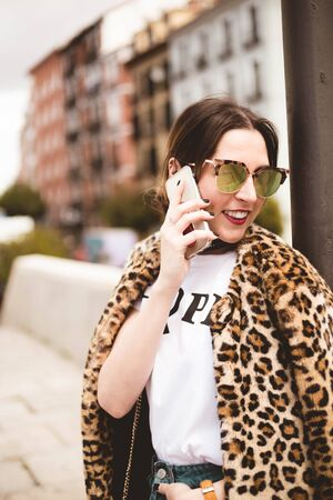 Portrait of a pretty smiling woman talking on the phone wearing a wearing trendy animal, leopard print faux fur coat, stylish sunglasses in street of Madrid city. Copy space for text Imagens