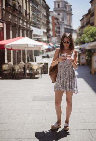 Beautiful young tourist woman walking in the street using a smartphone in Madrid city center, Spain