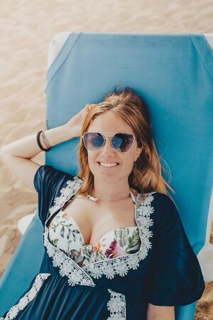 Young blonde woman with shot hair lying in a blue hammock with sunglasses smiling and enjoying the beach