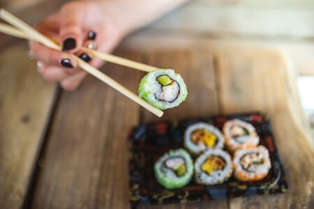 Unrecognized woman hand and tasty sushi rolls at wooden table, space for text. Food delivery Stock fotó
