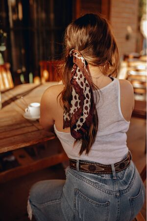 Rear view of a sexy young brunette woman with a ponytail and a bandana sitting on her back on a terrace drinking a cup of coffee in the afternoon. 스톡 콘텐츠