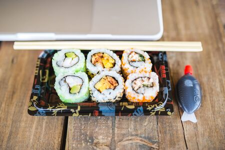 Top View of Vintage handmade Wood Table with Asian Sushi and laptop Stock Photo