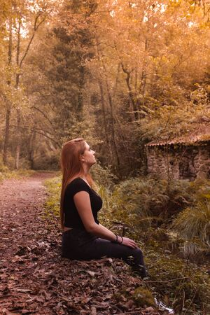 Side view of dreaming redhead woman sitting in the autumnal forest and river on background at sunset. Sad girl depressed, thoughtful and pensive. Lifestyle concept. 版權商用圖片
