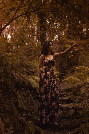 Tender woman in a black vintage dress touching leaves against the background of fiery autumn nature. Artistic Photography. Woman in dress on background of autumn foliage.