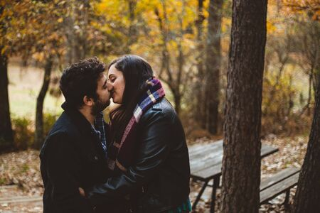 Couple in love kissing on autumn in the autumnal forest, enjoying a beautiful day. Couple kissing in the colorful orange and yellow park.