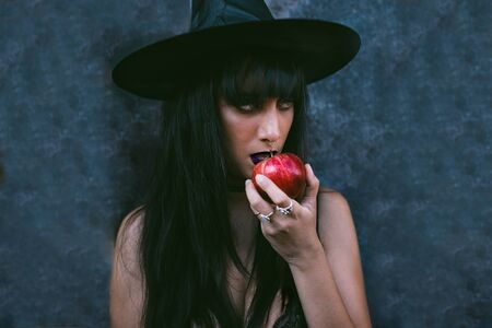 Young Halloween witch woman portrait eating a red apple. Beauty Angry Vampire Witch lady with black mouth in the darkness, wearing a witch hat. Mysterious Serious model girl with Halloween make up.