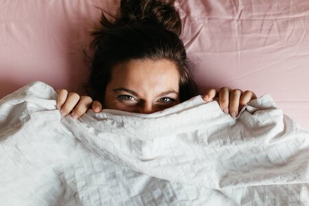 Playful young woman with beautiful eyes hiding face under blanket while lying in cozy bed, pretty curious girl feeling shy peeking from duvet, covering with white sheet, head shot close up. Top view