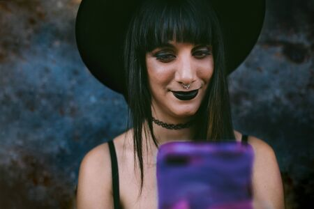 Young happy Halloween witch woman using smart phone. Beauty Witch lady with black mouth in the darkness, wearing a witch hat. Model girl with costume and Halloween make up. Dark background.
