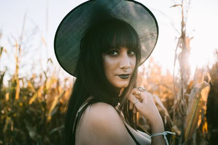 Halloween costume witch girl portrait in a cornfield at sunset. Beautiful serious young woman in witches hat with long black hair and dark lips. Magic forest background. Halloween holiday concept