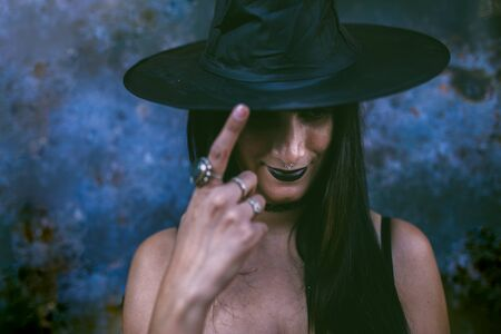 Young happy Halloween witch woman smiling and touching her witch hat. Beauty Witch lady with black mouth in the darkness. Serious model girl with costume and Halloween make up. Dark background.