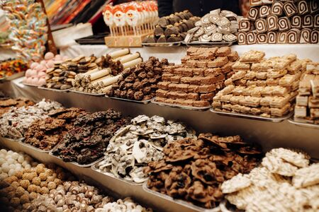 Child pointing sweets and chocolates at christmas market in Budapest, Hungary. Closeup on candy, chocolate & marzipan stall on market shop, fair or exhibition background picture. Reklamní fotografie