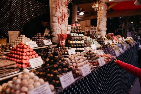 Child pointing sweets and chocolates at christmas market in Budapest, Hungary. Closeup on candy, chocolate & marzipan stall on market shop, fair or exhibition background picture. Imagens