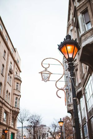 Christmas street decoration. Warm street lamp. Christmas lights In Budapest, Hungary between Christmas and New Years Eve. Lantern and residential real estate in downtown. Festive concept. Stok Fotoğraf