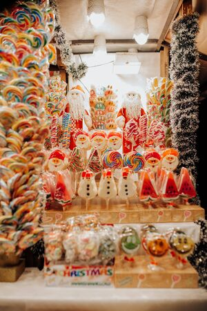 A vendor sells artisan chocolate, noel and watermelon lollipops and biscuits for Christmas and St. Nicholas Day at the Budapest Christmas market.