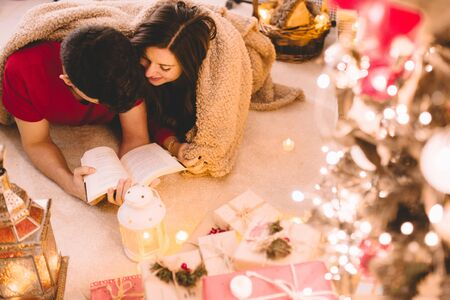 Top view of relaxing couple covered by a soft and cozy blanket at home reading a book together under the fireplace with candles, presents and decorated tree. Winter holiday and Merry christmas concept Stock Photo
