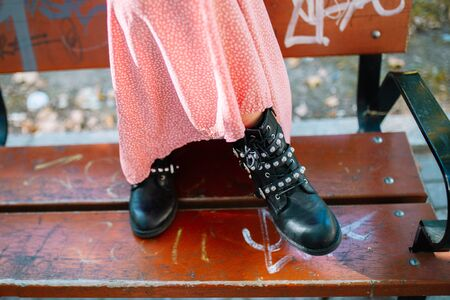 Woman's Black Leather Ankle Boots With Straps, Metal Studs And Zipper, Shot in a bench with graffiti on the street. Banque d'images