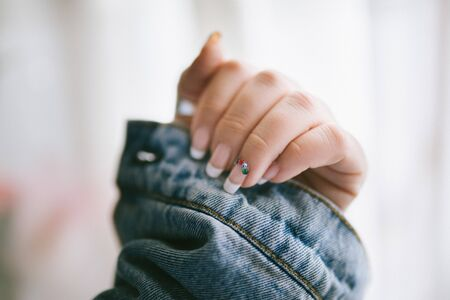 Elegant and long lasting woman french manicure with colorful beads and denim jacket. Lady hand with french manicure. Beauty female nails. Femininity and Beauty concept